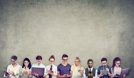 Groep multiculturele mensen die door digitale mobiele gadgets wordt verbonden te gebruiken stock afbeelding