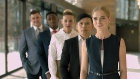 Groep multiraciaal commercieel team die zich op een rij in de hal bevinden stock videobeelden