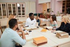 Groep multiraciale mensen die met boeken in universiteitsbibliotheek bestuderen stock foto