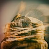 Groep muntstukken één euro in een glaskruik Euro geld Terug vaag Stock Fotografie