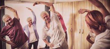 Groep oudsten die oefeningen met verpleegster doen stock afbeeldingen