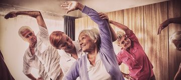 Groep oudsten die oefeningen met verpleegster doen royalty-vrije stock afbeelding