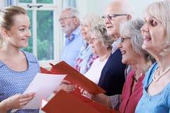 Groep Oudsten met Leraar Singing In Choir samen stock fotografie