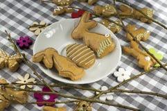 Groep peperkoekdieren en symbolen op witte plaat op geruit tafelkleed, twee konijntjes in liefde, paaseijacht royalty-vrije stock afbeelding