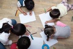 Groep peuterstudent en leraar die op papier in kunstklasse trekken Terug naar school en onderwijsconcept Mensen en levensstijlen royalty-vrije stock afbeelding