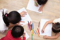 Groep peuterstudent en leraar die op papier in kunstklasse trekken Terug naar school en onderwijsconcept Mensen en levensstijlen stock afbeeldingen