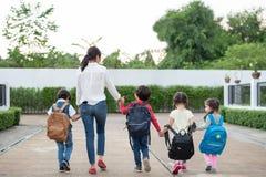 Groep peuterstudent en leraarsholdingshanden en het lopen aan huis Het mamma brengt haar kinderen gaat samen naar school Terug na stock foto's