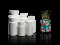 Groep plastic kleine flessen tegen een glasflesje met pillen. Stock Fotografie