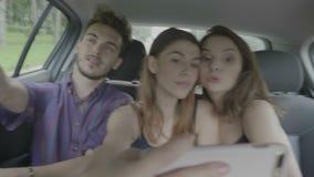 Groep reisvrienden die uit samen binnenkantauto hangen die selfie met smartphone nemen die wegreis van het posten op sociale medi stock videobeelden