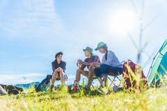Groep reizigers die en picknick in de voorgrond van het weidegebied kamperen doen Berg en meerachtergrond Mensen en levensstijlen stock afbeeldingen