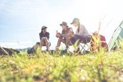 Groep reizigers die en picknick in de voorgrond van het weidegebied kamperen doen Berg en meerachtergrond Mensen en levensstijlen royalty-vrije stock foto