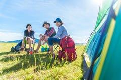Groep reizigers die en picknick in weide met tentvoorgrond kamperen doen Berg en meerachtergrond Mensen en levensstijlen stock afbeelding