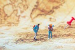 Groep reizigers miniatuurcijfers met rugzak die zich op oude kaart bevinden royalty-vrije stock afbeelding