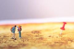 Groep reizigers miniatuurcijfers met rugzak die zich op oude kaart bevinden stock afbeeldingen
