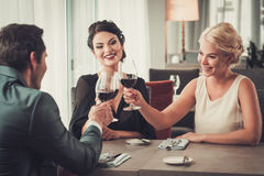 Groep rijke mensen die glazen rode wijn in restaurant clinking Stock Foto's