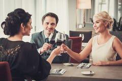 Groep rijke mensen die glazen rode wijn in restaurant clinking Stock Foto
