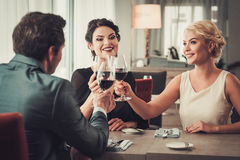 Groep rijke mensen die glazen rode wijn in restaurant clinking Stock Fotografie