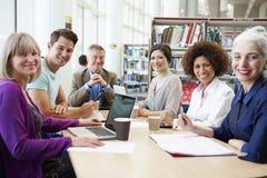 Groep Rijpe Studenten die op Project in Bibliotheek samenwerken Stock Afbeeldingen