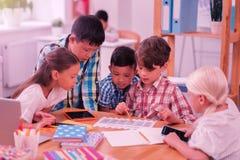 Groep schoolkinderen die hun nieuw tijdschema onderzoeken royalty-vrije stock foto