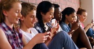 Groep schoolvrienden die mobiele telefoon 4k met behulp van stock videobeelden