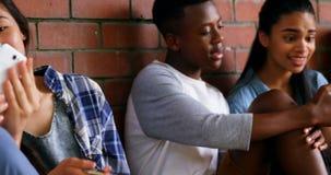 Groep schoolvrienden die mobiele telefoon 4k met behulp van stock footage