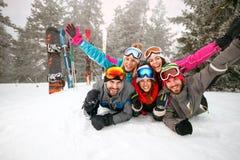 Groep skiërs die op sneeuw liggen en pret hebben Stock Foto's