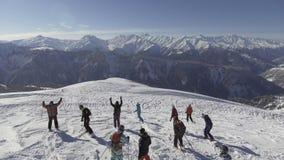 Groep skiërs en snowboardersglijdende bewegingen neer weg van de sneeuw afgedekte bovenkant van de skiheuvel stock videobeelden