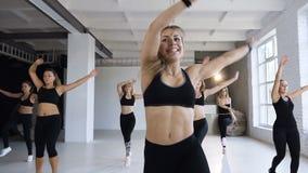 Groep sportieve mensen die in een geschiktheidsklasse opleiden - Kaukasische groep atleten jonge vrouwen die geschiktheid of stap stock video