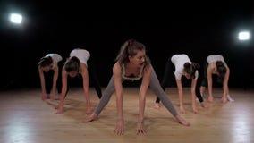 Groep sportieve mensen in een gymnastiek die - Meisjesgroep die atleten alvorens een zitting van de trainingyoga te beginnen uitr stock videobeelden