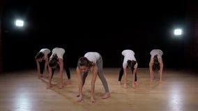 Groep sportieve mensen in een gymnastiek die - Meisjesgroep die atleten alvorens een zitting van de trainingyoga te beginnen uitr stock video