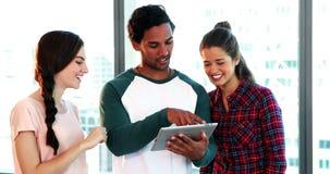 Groep stafmedewerkers die over digitale tablet bespreken stock video