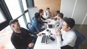 Groep strategiemanagers die laatste bedrijfsrapporten van uitwisselingen over laptop lezen stock footage