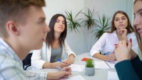 Groep studenten die aan examen, onderzoek of quiz samen in instituut voorbereidingen treffen stock videobeelden