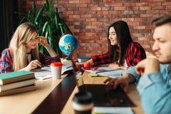 Groep studenten die bij de lijst samen bestuderen stock afbeelding