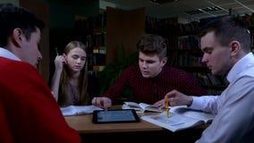 Groep studenten die bij een lijst in een bibliotheek zitten stock video