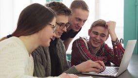 Groep studenten die en laptop het scherm spreken bekijken stock videobeelden