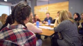 Groep studenten die in klaslokaal van universiteitsuniversiteit bestuderen mensen die seminarie van leraarsbus luisteren te sprek stock video