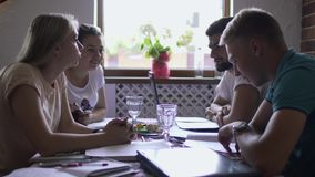 Groep studenten die samen aan examen op universiteit in de koffie voorbereidingen treffen stock video