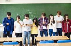 Groep studenten die slimme mobiele telefoons in klaslokaal met behulp van royalty-vrije stock afbeelding