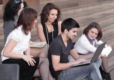 Groep studenten die voor tests voorbereidingen treffen die laptop met behulp van stock afbeeldingen