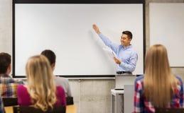 Groep studenten en glimlachende leraar met blocnote Stock Afbeeldingen