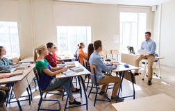 Groep studenten en leraar met documenten of tests Stock Afbeeldingen