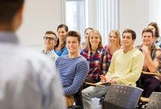 Groep studenten en leraar met notitieboekje Stock Afbeeldingen