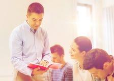 Groep studenten en leraar met notitieboekje Stock Afbeelding
