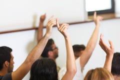 Groep studenten gezette hand omhoog in klassenruimte Royalty-vrije Stock Foto's