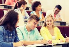 Groep studenten met notitieboekjes in lezingszaal stock fotografie