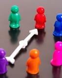 Groep stuk speelgoed volkeren en witte pijl Stock Afbeeldingen