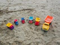 Groep stuk speelgoed werkende vrachtwagens op een zandig strand Stock Foto