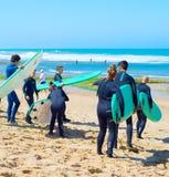 Groep surfer het gaande surfen Stock Foto's