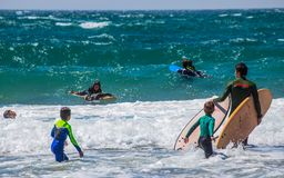 Groep surfers op Cascais-strand op een zonnige dag, Portugal royalty-vrije stock fotografie